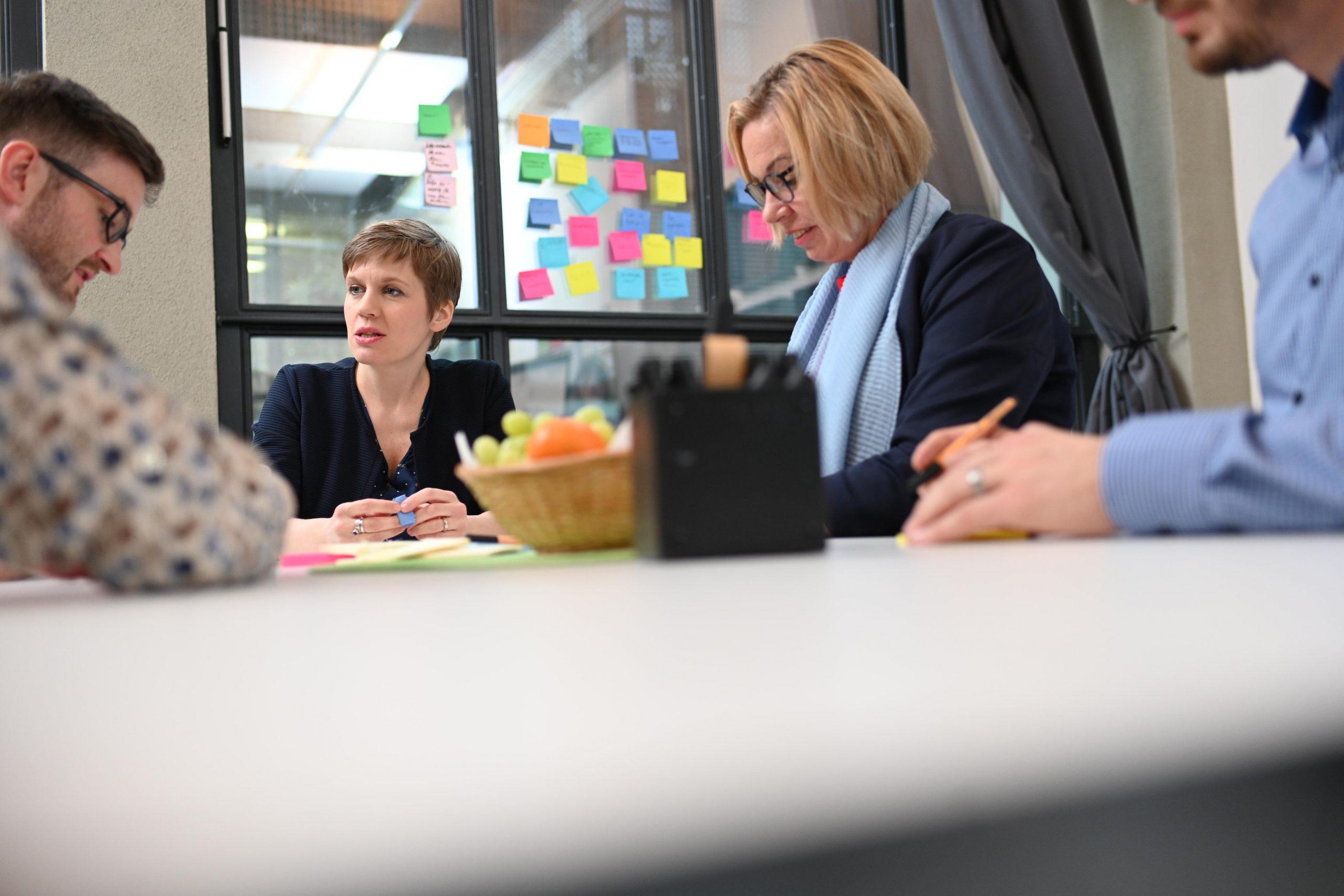 Teammitglieder sitzen am Tisch und schreiben Postits zu Veränderungsprozessen
