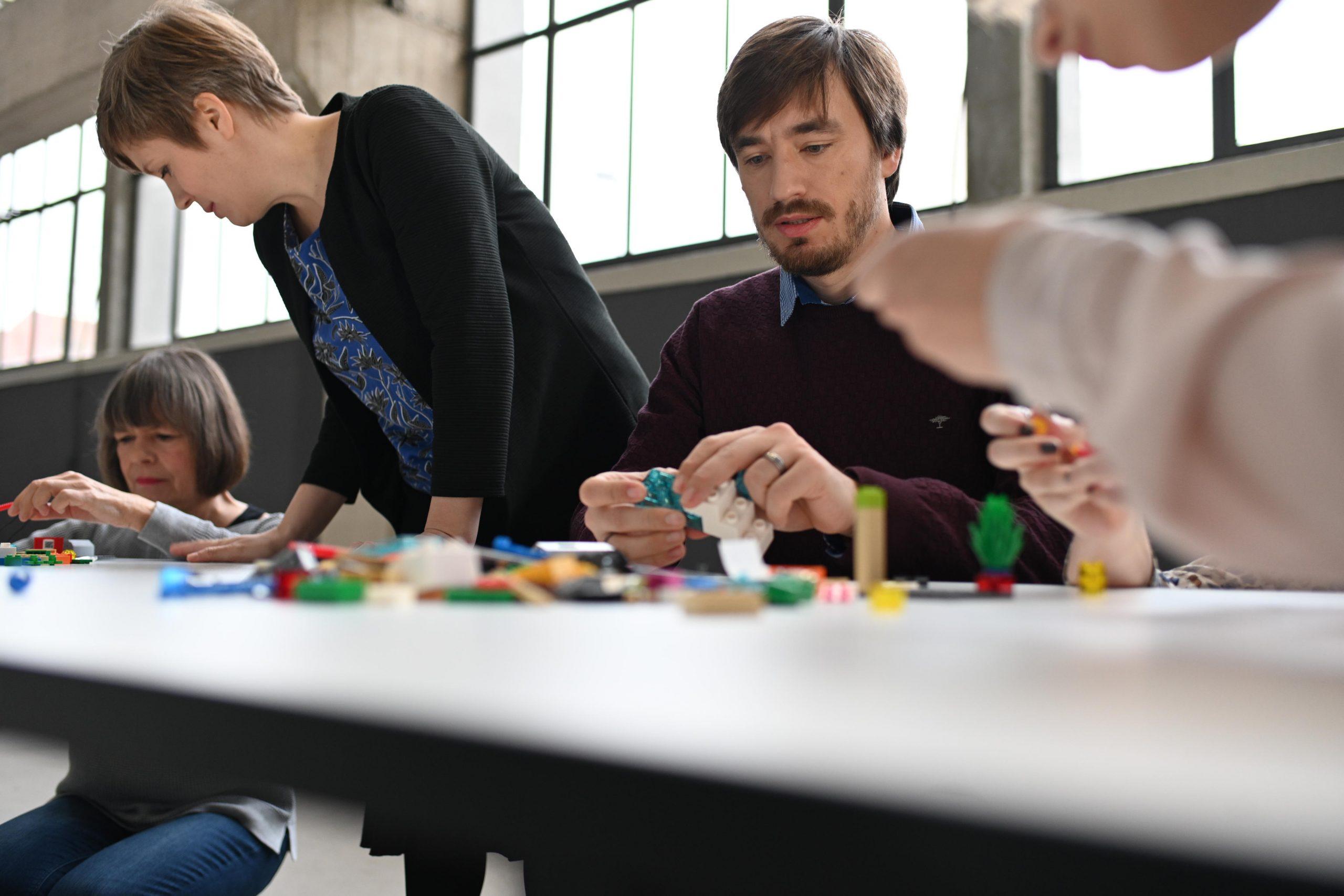 Teilnehmer im Teamworkshop arbeiten mit Lego