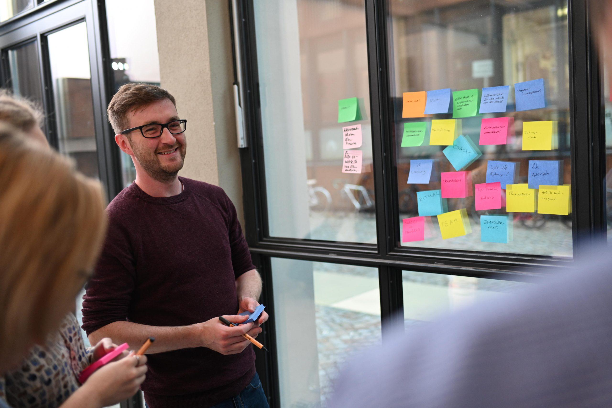 Teilnehmer eines Change Management Prozesses vor einer Wand aus Postits